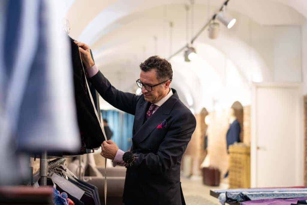 Senior male fashion designer making the measurement in his atelier of his suit