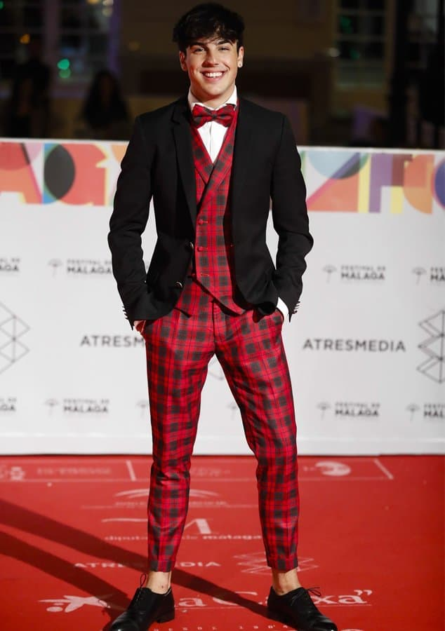 Óscar Casas con chaleco y pantalón de cuadros escocés y americana negra con botón metálico.